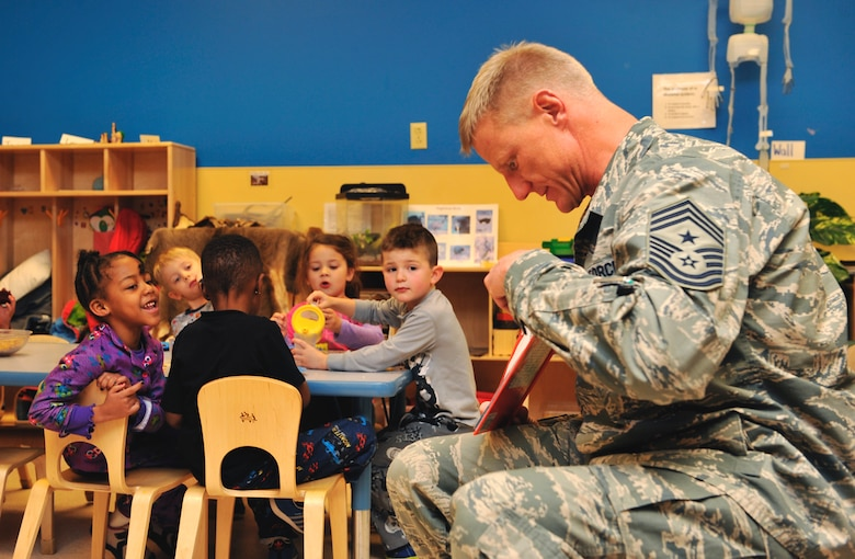 Chief Master Sgt. Craig S. Hall, 460th Space Wing command chief, reads a Dr. Seuss book to a preschool class Feb. 28, 2014, at the A-Basin Child Development Center on Buckley Air Force Base, Colo. Hall read to the children during their snack time to celebrate Dr. Seuss's birthday. (U.S. Air Force photo by Airman 1st Class Samantha Saulsbury/Released)