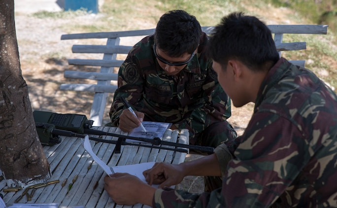 Philippine Air Force airmen discuss target locations for precision air strikes at Crow Valley Bombing Complex, Republic of the Philippines Feb. 26, as part of close-air support training during Exercise Haribon Tempest 2014. Focused on close-air support, section engaged maneuvering training and combined combat capabilities; HT 14 is a small-scale bilateral exercise between the United Sates Marine Corps and the Philippine Air Force.