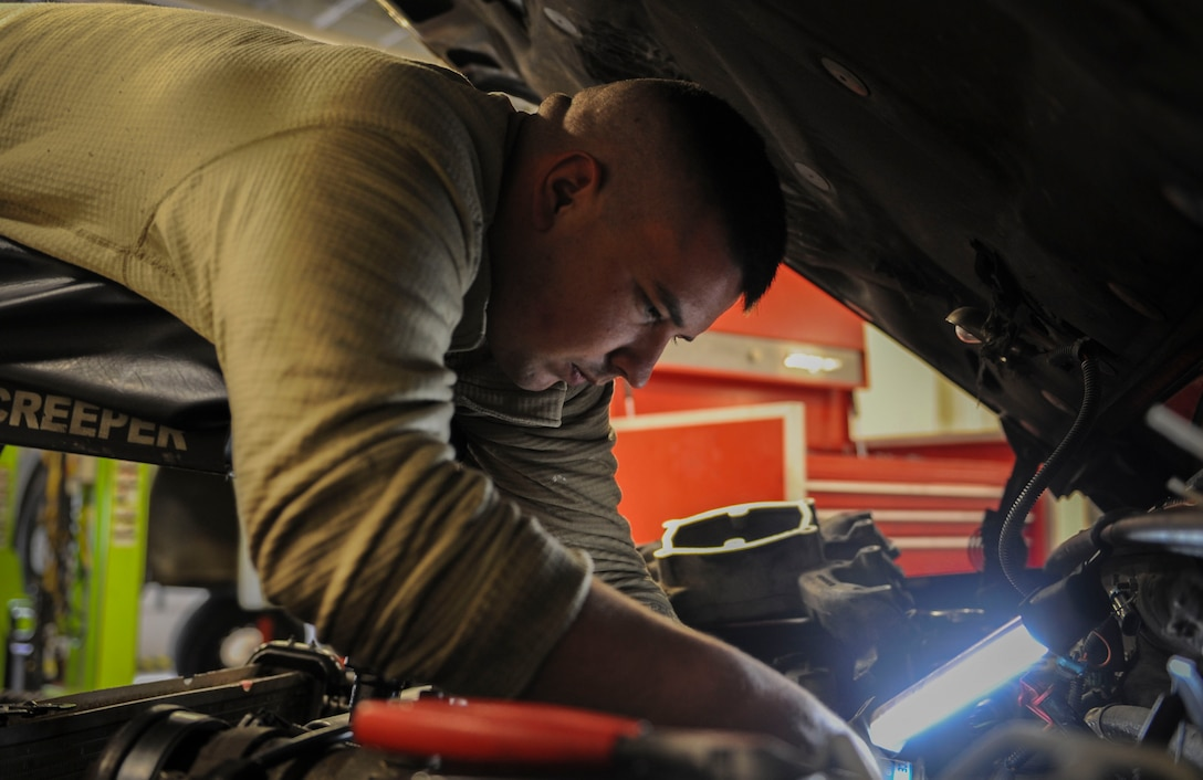 U. S. Air Force Senior Airman Josh Flodder, 23d Logistics Readiness Squadron vehicle vehicular equipment maintenance journeyman, works on a truck engine at Moody Air Force Base, Ga., March 5, 2014. Flodder used a topside creeper allowing him to reach the part he needed to fix. (U.S. Air Force photo by Airman 1st Class Alexis Millican/Released)