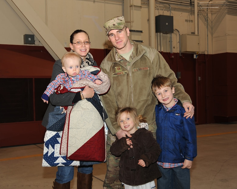 While bundled up with a quilt made by the Mid Valley Quilt Guild, Tech. Sgt. Ken Safe and his family pose for a photo following the mobilization ceremony held at the Portland Air National Guard Base, Ore., March 1. (Air National Guard photo by Master Sgt. Shelly Davison, 142nd Fighter Wing Public Affairs/Released)