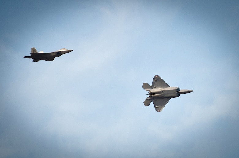 Two U.S. Air Force F-22s from the Raptor Demonstration Team practice an aerobatic maneuver as they fly over the Kentucky Air National Guard Base in Louisville, Ky., on April 14, 2011. The team is set to appear again in the 2014 Thunder Over Louisville Air Show. (U.S. Air National Guard photo by Maj. Dale Greer)
