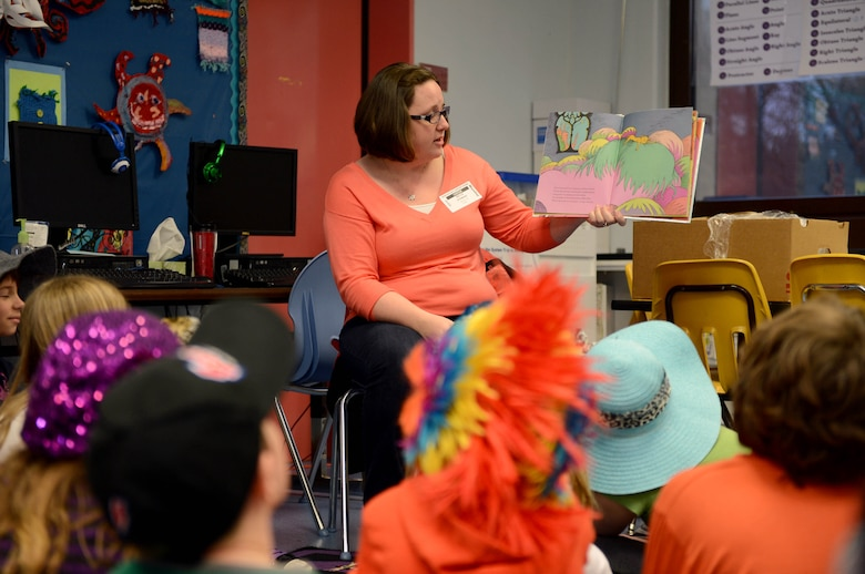 Becca Stewart, wife of 1st Lt. Jason Stewart, 606th Air Control Squadron, reads to elementary school children during a Read Across America event at Spangdahlem Air Base, Germany, March 3, 2014. Students across America celebrate the birth of Dr. Seuss by reading books March 2. (U.S. Air Force photo by Airman 1st Class Kyle Gese/Released)
