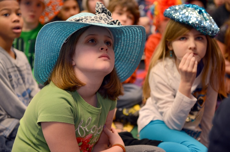 Hannah Sweazey, Spangdahlem Elementary student, listens to a volunteer read a Dr. Seuss book during a Read Across America event at Spangdahlem Air Base, Germany, March 3, 2014. National Read Across America is a day that celebrates the birthday of Dr. Seuss. (U.S. Air Force photo by Airman 1st Class Kyle Gese/Released)