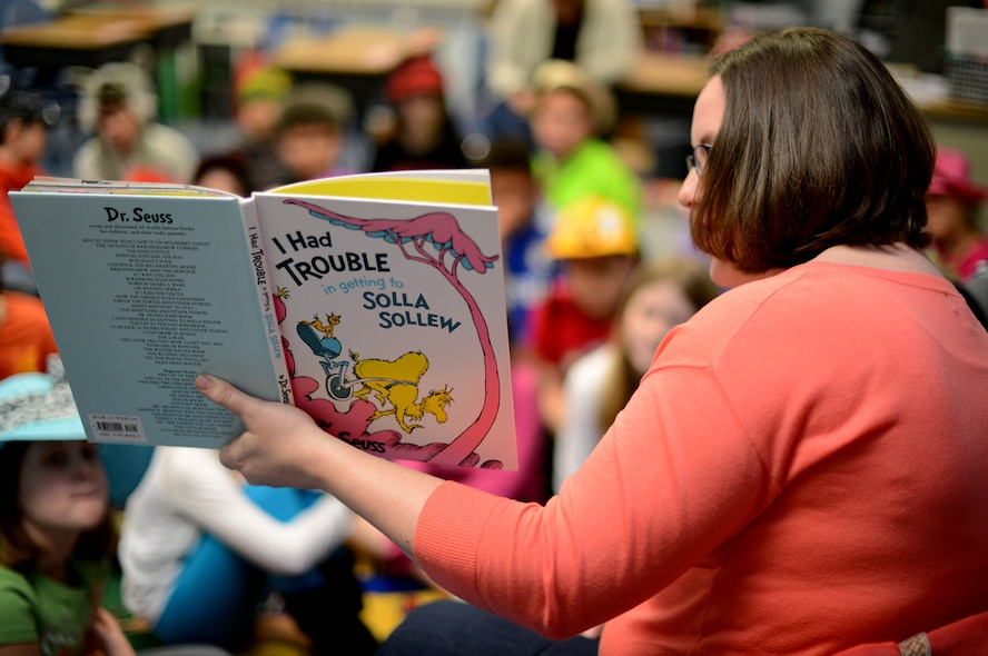 Becca Stewart, wife of 1st Lt. Jason Stewart, 606th Air Control Squadron, reads to elementary school children during a Read Across America event at Spangdahlem Air Base, Germany, March 3, 2014. Read Across America was held in honor of Dr. Seuss's birthday, March 2, 1904. (U.S. Air Force photo by Airman 1st Class Kyle Gese/Released)