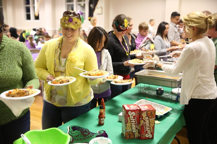 Family members dress up for the Mardi Gras-themed No Dough Dinner at the USO of North Carolina, Jacksonville Center, Feb. 24. The dinner is held at the end of the month for service members E-1 through E-6 who are struggling to make ends meet.
