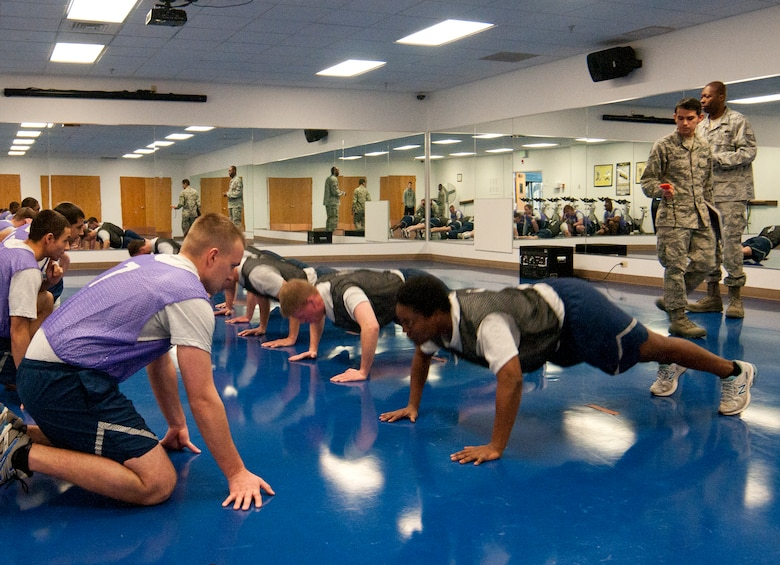 Airmen take the pushup portion of the Air Force fitness assessment, which entails doing as many pushups as possible within one minute, March 4, 2014, in the Indepence Hall Fitness Center on F.E. Warren Air Force Base, Wyo. Test takers count the number of pushups a wingman performs correctly, and then the two switch and the other Airman counts while the first counter performs pushups. The 90th Force Support Squadron Fitness Improvement Program intends to help Airmen who want to improve their fitness assessment scores, and increasing the number of pushups they can perform is one way to improve. (U.S. Air Force photo by Airman 1st Class Jason Wiese)