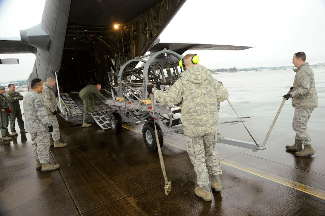 Oregon Air National Guard Logistical Readiness Squadron members Tech. Sgt. Sam Riggs and Tech. Sgt. Michael Morris, 142nd Fighter Wing, load cargo into a C-130 Hercules, at the Portland Air National Guard Base, Ore., Feb. 27, 2014. (U.S. Air National Guard photo by Tech. Sgt. John Hughel/Released)