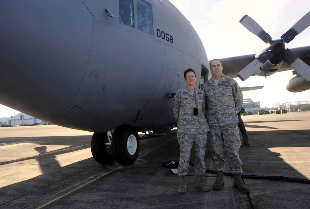 Oregon Air National Guard Logistical Readiness Squadron members Senior Master Sgt. Pam Pittman and Tech. Sgt. Michael Morris, 142nd Fighter Wing, pause for a photograph next to a C-130 Hercules, at the Portland Air National Guard Base, Ore., Feb. 27, 2014. (U.S. Air National Guard photo by Tech. Sgt. John Hughel/Released)