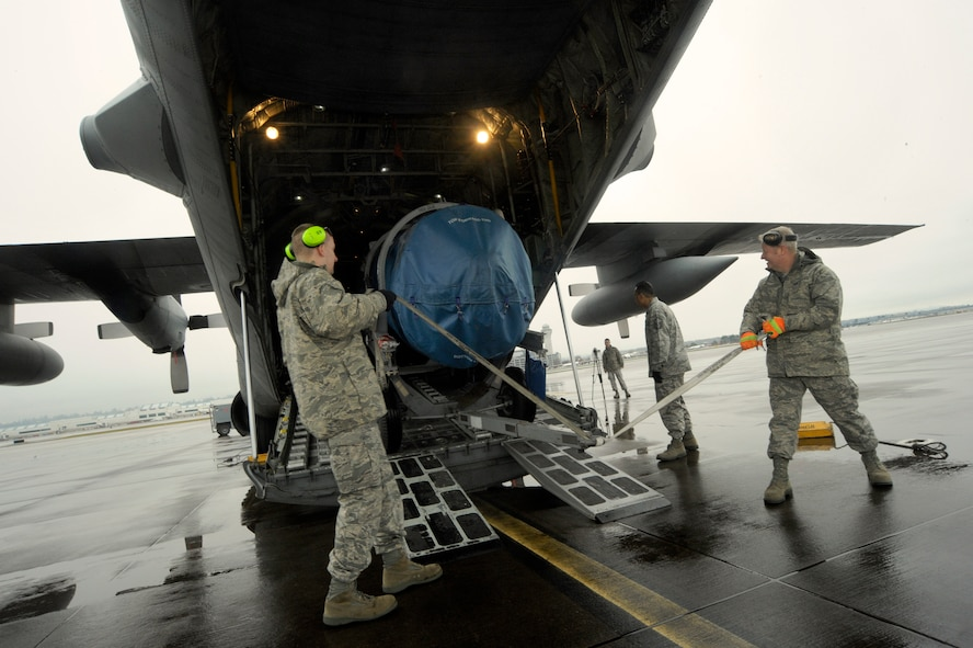 Oregon Air National Guard airmen Senior Airman Ryan Rosso (left) and Staff Sgt. Dan Beard (right) move equipment into a C-130 Hercules, at the Portland Air National Guard Base, Ore., Feb. 27, 2014. Rosso and Beard, 142nd Fighter Wing Logistics Readiness Squadron members, are packing equipment that will be used in the Red Flag exercise at Nellis Air Force Base, Nev. (U.S. Air National Guard photo by Tech. Sgt. John Hughel/Released)