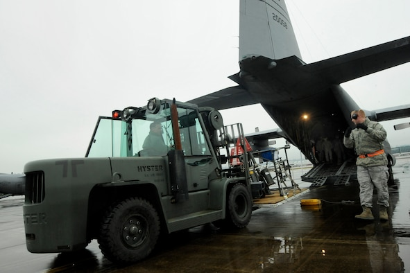 Oregon Air National Guard members Tech. Sgt. Sam Riggs spots Tech. Sgt. Michael Jones as he moves a fork lift into place as they load a C-130 Hercules, at the Portland Air National Guard Base, Ore., Feb. 27, 2014. Jones and Riggs, 142nd Fighter Wing Logistics Readiness Squadron members, are packing equipment that will be used in the Red Flag exercise at Nellis Air Force Base, Nev. (U.S. Air National Guard photo by Tech. Sgt. John Hughel/Released)