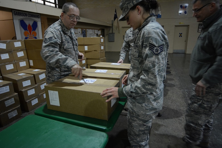 The 115th Force Support Squadron services Airmen open boxes of food in preparation for lunch during Cajun Care 2014 in Abbeville, La., March 4, 2014. The team of six brought down 11 pallets of Unitized Group Rations. Three boxes of UGRs contained enough food to feed 50 people. The Airmen fed approximately 100 people per day during the 10-day mission using the Single Pallet Expeditionary Kitchen they brought down with them from Madison, Wis. (Air National Guard photo by Senior Airman Andrea F. Liechti)