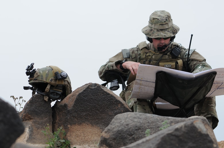 A picture of U.S. Air Force Tech. Sgt. Wayne White, a tactical air control party airman using a range map and radio.