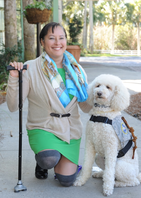 Retired Capt. Mary McGriff poses with her service dog, Courage, during an Air Force Reserve Yellow Ribbon Program training event Jan. 25, 2014, in Hilton Head Island, S.C. McGriff was diagnosed with post-traumatic stress disorder following a 2003-2004 deployment to Iraq and now speaks to Yellow Ribbon participants about how Courage helps her overcome flashbacks and panic attacks. (U.S. Air Force photo by Peter R. Miller)