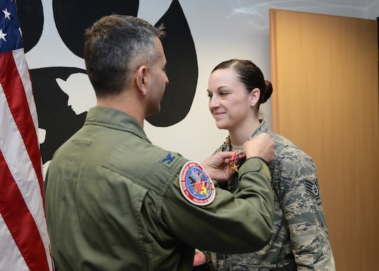 """U.S. Air Force Col. David Julazadeh, 52nd Fighter Wing commander, presents a Bronze Star to Staff Sgt. Shannon Hennessy, 52nd Security Forces Squadron military working dog handler, at the MWD kennel on Spangdahlem Air Base, Germany, Feb. 27, 2014. Hennessy and her MWD """"Katya"""" recently returned from a six-month deployment with the Combined Joint Special Operations Task Force in Afghanistan. (U.S. Air Force photo by Staff Sgt. Chad Warren/released)"""