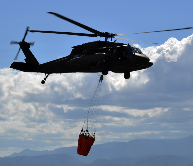 A UH-60 Blackhawk helicopter assigned to Joint Task Force-Bravo's 1-228th Aviation Regiment carries a Bambi bucket en route to an aerial firefighting mission in Honduras.  The 1-228th utilized the Bambi buckets to battle a fire that was threatening villages near Soto Cano Air Base, Honduras on the evening of March 4, 2014.  Two Blackhawks flew under night vision goggles and dropped more than 10,000 gallons of water over a four-hour span to extinguish the blaze.  (U.S. Air Force photo by Capt. Zach Anderson)
