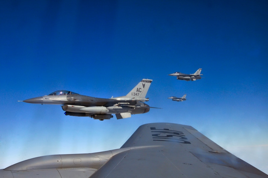 Three U.S Air Force F-16 Fighting Falcons from the New Jersey Air National Guard's 177th Fighter Wing fly just off the wingtip of a 191st Air Refueling Squadron KC-135 Stratotanker en route to Operation Snowbird (OSB) training at Davis-Monthan Air Force Base, Ariz., on Feb. 19, 2014. Southern Arizona provides optimal weather conditions and ample ranges that mirror the environment found downrange, and OSB hosts an average of 10-12 units per year with two to 12 aircraft per visit for an average of two weeks. (U.S. Air National Guard photo by Master Sgt. Andrew Moseley/Released)
