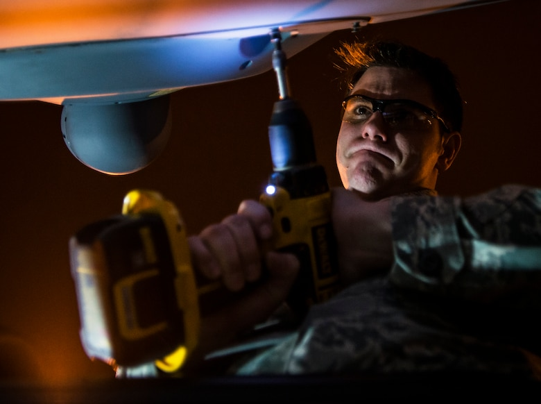 Staff Sgt. Ryan Jordan uses a power drill to remove screws that hold an infrared countermeasure device on a C-17 Globemaster III March 3, 2014, at Joint Base Charleston, S.C. The infrared countermeasure is used to stop homing missiles or devices from striking the aircraft. Jordan is a 437th Aircraft Maintenance Squadron electronic warfare systems technician. (U.S. Air Force photo/Senior Airman Dennis Sloan)