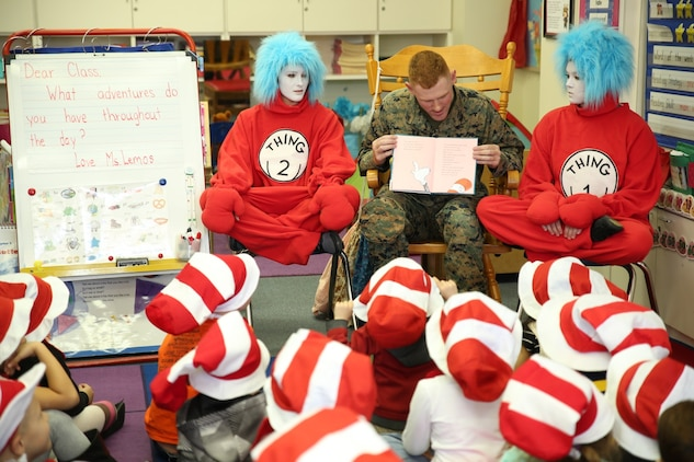 Lance Cpl. Tommy Fears, a flight equipment technician with Marine Aviation Logistics Squadron 12, flanked by Thing 1 and Thing 2, reads to a kindergarten class at Matthew C. Perry Elementary School aboard Marine Corps Air Station Iwakuni, Japan, for Read Across Department of Defense Education Activity Day March 3, 2014. Read Across DoDEA Day is an event which recognizes the birthday of Theodor Seuss Geisel, better known as Dr. Seuss, and focuses on getting children to read.