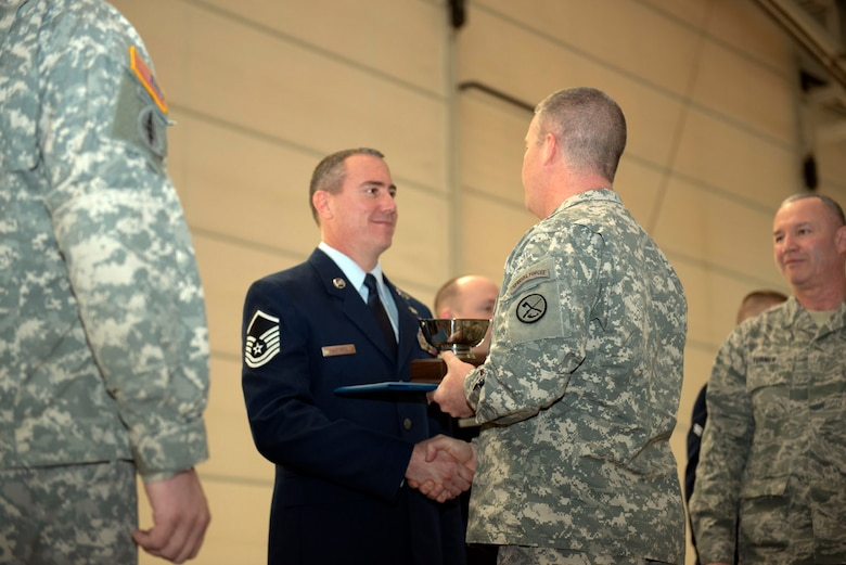 Maj. Gen. James A. Hoyer, Adjutant Generla of West Virginia, presents the James Kemp McLaughlin trophy, awarded to West Virginia's top airman, to Master Sgt. David Martens during an awards ceremony for the Wing's Outstanding Airmen of the Year, March 1. (Air National Guard photo by Tech. Sgt. Michael Dickson/Released)