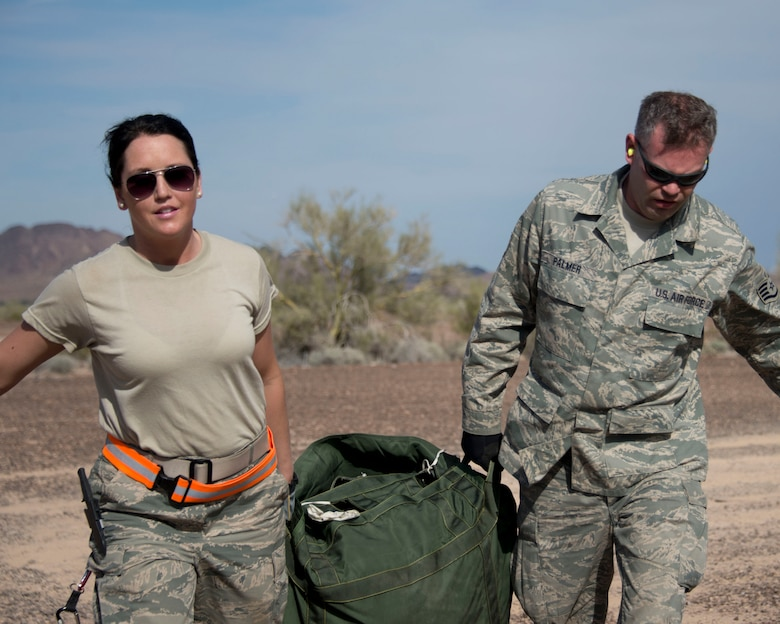 Staff Sgt. Crystal DuBois, left, and Staff Sgt. Alex Palmer drag a packed parachute in Yuma, Ariz., Feb. 25, 2014. DuBois and Palmer are two of four assigned to the recovery team. This team is responsible for recovering the training pallets released from the Minnesota Air National Guard C-130 Hercules aircraft.  (U.S. Air National Guard photo by Tech. Sgt. Amy M. Lovgren/Released)