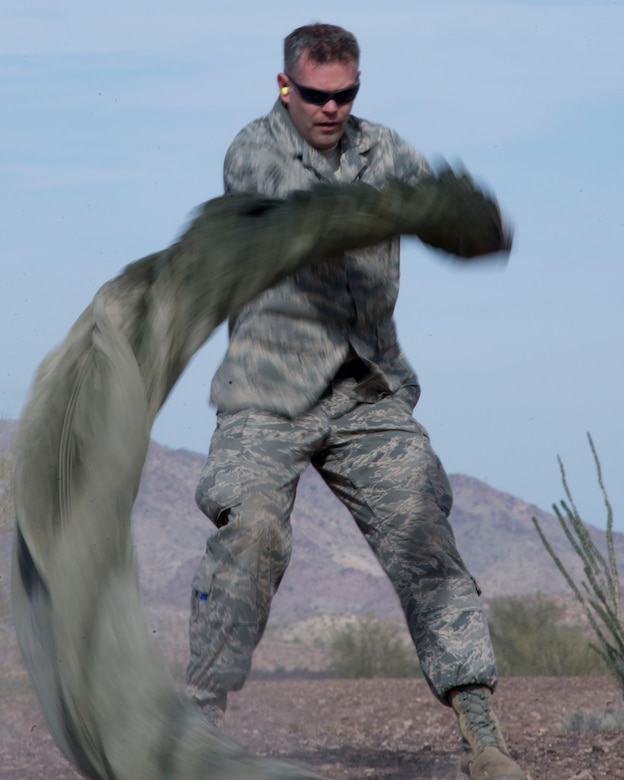 Staff Sgt. Alex Palmer, 133rd Small Air Terminal Section, spins a parachute in Yuma, Ariz., Feb. 25, 2014. Palmer is one of four assigned to the recovery team. This team is responsible for recovering the training pallets released from the Minnesota Air National Guard C-130 Hercules aircraft. (U.S. Air National Guard photo by Tech. Sgt. Amy M. Lovgren/Released)