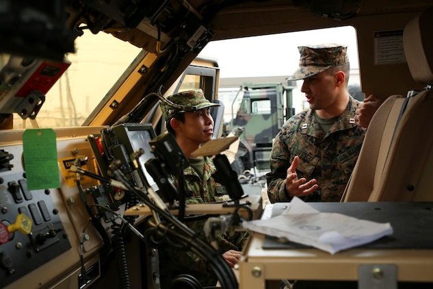 Capt. George Ivascu, motor transport company commander with Marine Wing Support Squadron 171, talks to Capt. Yushi Nakamura, officer in charge of the English program with the Japan Ground Self-Defense Force, while looking through a Mine-Resistant Ambush Protected All-Terrain vehicle, Feb. 27, 2014, during an English clinic aboard Marine Corps Air Station Iwakuni, Japan. The English clinic is an annual event hosted by the station Public Affairs Office as part of a weeklong English seminar held for members of the JGSDF.