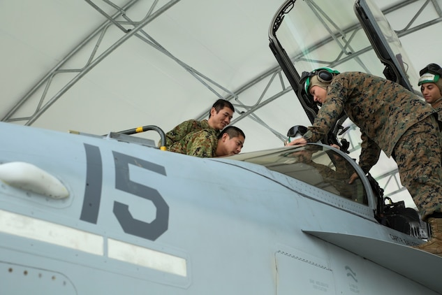 Members of the Japan Ground Self-Defense Force look in the cockpit of an F/A-18D Hornet, Feb. 27, 2014, during an English clinic aboard Marine Corps Air Station, Japan. The F/A-18D Hornet is with Marine All-Weather Fighter Attack Squadron 224 from MCAS Beaufort, S.C. as part of the Unit Deployment Program.