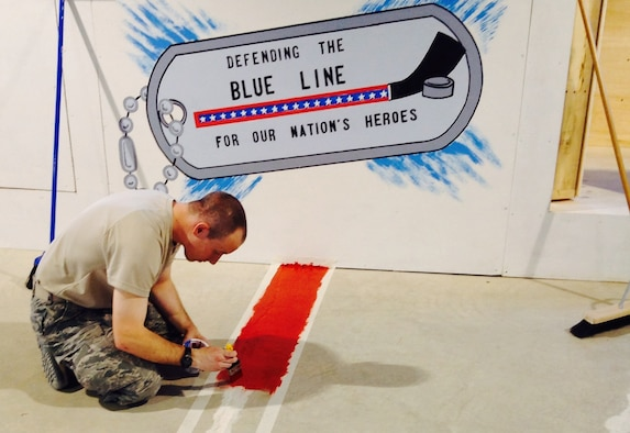 Airman 1st Class Joshua Hanson paints the center red line on his hockey rink in an undisclosed location in Southwest Asia. Hanson handcrafted an entire hockey rink with the help of volunteers. Hanson is with the 386th Expeditionary Communication Squadron. (U.S. Air Force photo/Senior Airman Desiree W. Moye)