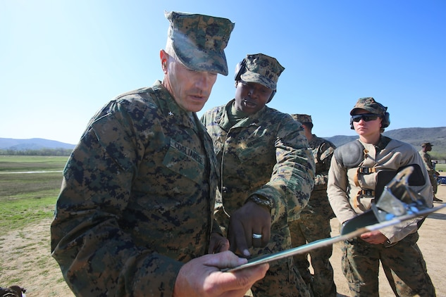 Gunnery Sgt. Jamil H. Dudley, a chemical, biological, radiological and nuclear defense specialist with Combat Logistics Regiment 1, 1st Marine Logistics Group, shows Brig. Gen. Vincent A. Coglianese, commanding general, 1st MLG, a roster detailing how his Marines performed during the 2014 Western Division matches aboard Marine Corps Base Camp Pendleton, Calif., March 5, 2014. Marines from CLRs 17, 1, 15 and 7th Engineer Support Battalion, 1st MLG, competed against approximately 200 Marines from throughout the west coast to prove their marksmanship skills with the M16 service rifle, the M4 carbine and the M9 service pistol , Feb 24 – March 7, 2014.