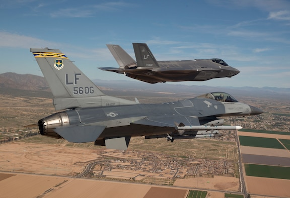 Maj. Justin Robinson flies the 56th Operations Group flagship F-16 Fighting Falcon as he escorts Luke Air Force Base's first F-35 Lightning II to the base March 10, 2014. The F-35 was flown by Col. Roderick Cregier, an F-35 test pilot stationed at Edwards AFB, Calif. Robinson is the 61st Fighter Squadron assistant director of operations. (U.S. Air Force photo/Jim Hazeltine)