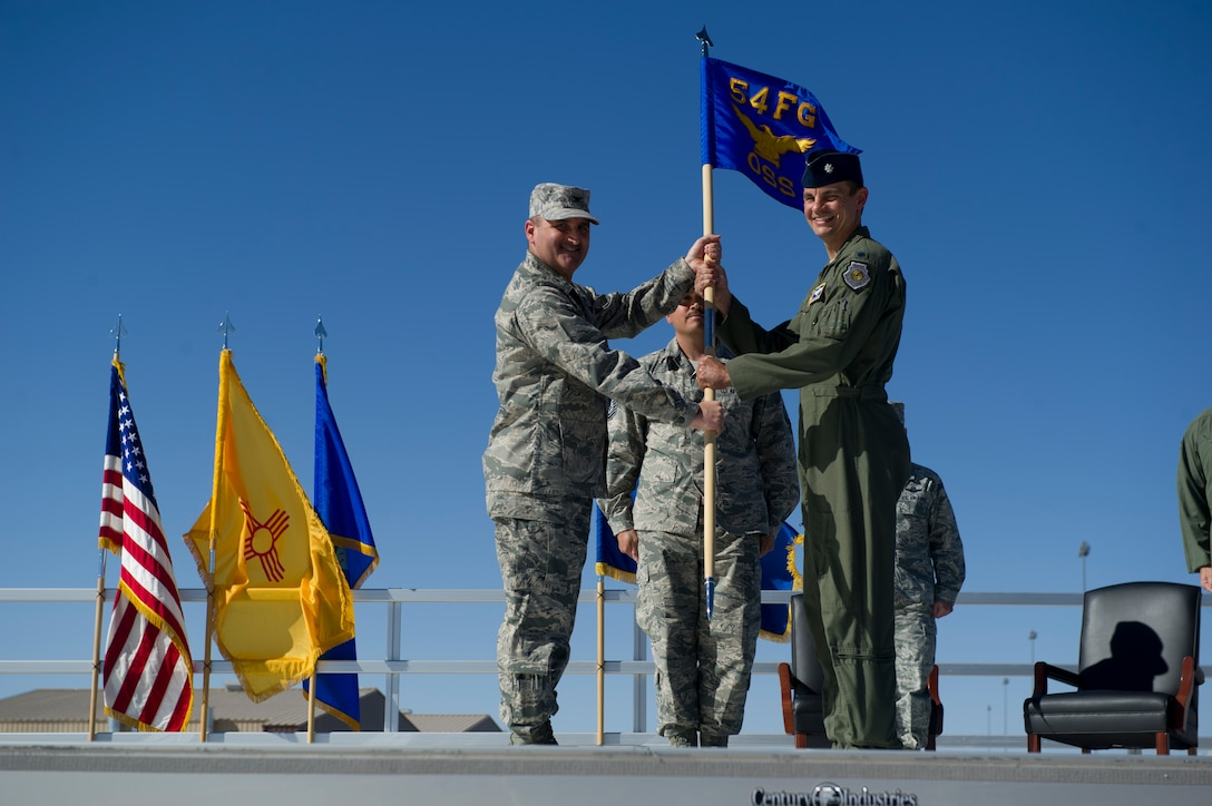 Col. Rodney Petithomme, 54th Fighter Group commander, passes the guidon of the 54th Operations Support Squadron to Lt. Col. Marshall Chalverus during the 54th Fighter Group activation ceremony at Holloman Air Force Base, N.M., March 11. The 54th Fighter Group, a tenant unit at Holloman, is a detachment the 56th Fighter Wing at Luke Air Force Base, Ariz., and will ultimately operate two F-16 Fighting Falcon aircraft training squadrons. The 54th Fighter Group plus three squadrons were activated at the ceremony: the 311th Fighter Squadron, the 54th Operations Support Squadron and the 54th Aircraft Maintenance Squadron. (U.S. Air Force photo by Airman 1st Class Chase A. Cannon/Released)