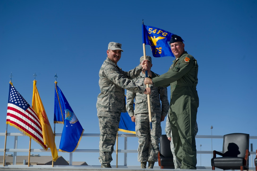 Col. Rodney Petithomme, 54th Fighter Group commander, passes the guidon of the 311th Fighter Squadron to Lt. Col. Scott Frederick during the 54th Fighter Group activation ceremony at Holloman Air Force Base, N.M., March 11. The 54th Fighter Group, a tenant unit at Holloman, is a detachment the 56th Fighter Wing at Luke Air Force Base, Ariz., and will ultimately operate two F-16 Fighting Falcon aircraft training squadrons. The 54th Fighter Group plus three squadrons were activated at the ceremony: the 311th Fighter Squadron, the 54th Operations Support Squadron and the 54th Aircraft Maintenance Squadron. (U.S. Air Force photo by Airman 1st Class Chase A. Cannon/Released)