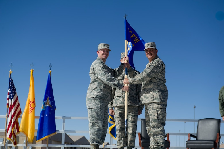Brigadier Gen. Michael Rothstein, 56th Fighter Wing commander, passes the guidon of the 54th Fighter Group to Col.l Rodney Petithomme during the 54th Fighter group activation ceremony at Holloman Air Force Base, N.M., March 11. The 54th Fighter Group, a tenant unit at Holloman, is a detachment the 56th Fighter Wing at Luke Air Force Base, Ariz., and will ultimately operate two F-16 Fighting Falcon aircraft training squadrons. The 54th Fighter Group plus three squadrons were activated at the ceremony: the 311th Fighter Squadron, the 54th Operations Support Squadron and the 54th Aircraft Maintenance Squadron. (U.S. Air Force photo by Airman 1st Class Chase A. Cannon/Released)