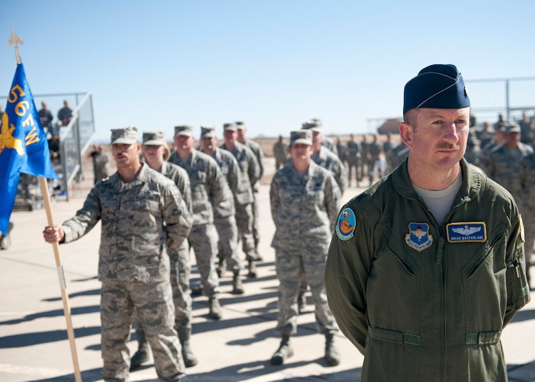 Lieutenant Col. Brian Macfarlane, 54th Operation Support Squadron director of operations, stands in formation with the new Airmen of the 54th Fighter Group at Holloman Air Force Base, N.M., March 11. The 54th Fighter Group, a tenant unit at Holloman, is a detachment the 56th Fighter Wing at Luke Air Force Base, Ariz., and will ultimately operate two F-16 Fighting Falcon aircraft training squadrons. The 54th Fighter Group plus three squadrons were activated at the ceremony: the 311th Fighter Squadron, the 54th Operations Support Squadron and the 54th Aircraft Maintenance Squadron. (U.S. Air Force photo by Senior Airman Daniel E. Liddicoet/Released)