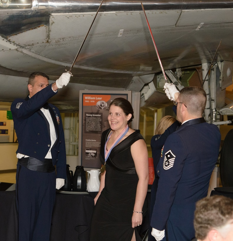 Coleen Gause, Spouse of the Year, walks through a saber team arch led by first sergeants to accept her award at the 446th Airlift Wing Annual Awards Banquet March 8 at Boeing's Museum of Flight in Seattle.  Mrs. Gause, mother of three, was nominated by her husband, 1st Lt. Gregory Gause, 313th Airlift Squadron pilot, because of her continued support and understanding she has shown for the past three years while he was in pilot training.  (Courtesy photo by David Lobban, Lobban Photography Inc.)