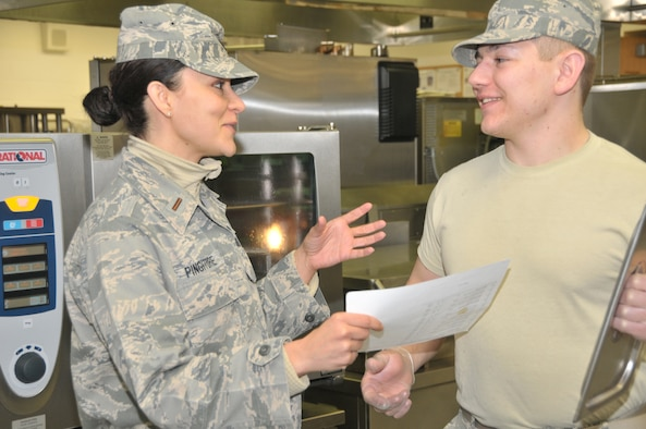 STRATTON AIR NATIONAL GUARD BASE, N.Y. -- Second Lt. Shannon Pingitore goes over a recipe card with Senior Airman Joshua Henderson during the March Unit Training Assembly on March 10, 2014 in the kitchen of the Base Dining Facility. Pingitore is a food service officer with the 109th Force Support Squadron's Services Flight. (Air National Guard photo by Tech. Sgt. Catharine Schmidt/Released)