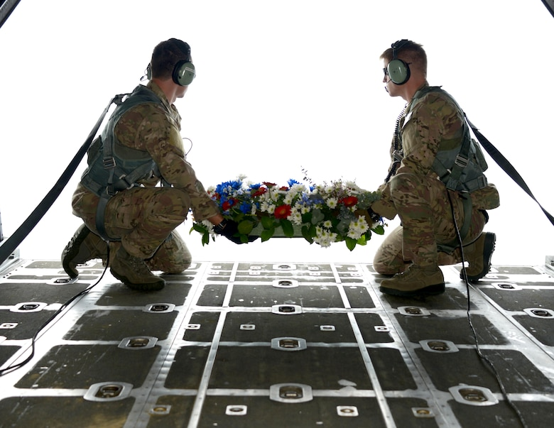 From left, Staff Sgt. Michael Wilson and Staff Sgt. Anthony Bliss, both loadmasters from the 1st Special Operations Squadron, prepare to drop the wreath from an MC-130H Combat Talon II off the coast of the Philippines Feb. 26, 2014 in memory of those who died in the crash of Stray 59.  The flight honors those who were lost 33 years ago when a 1st SOS MC-130E, call sign STRAY 59, crashed during an exercise killing eight crew members and 15 passengers. (U. S. Air Force photo by Tech. Sgt. Kristine Dreyer)