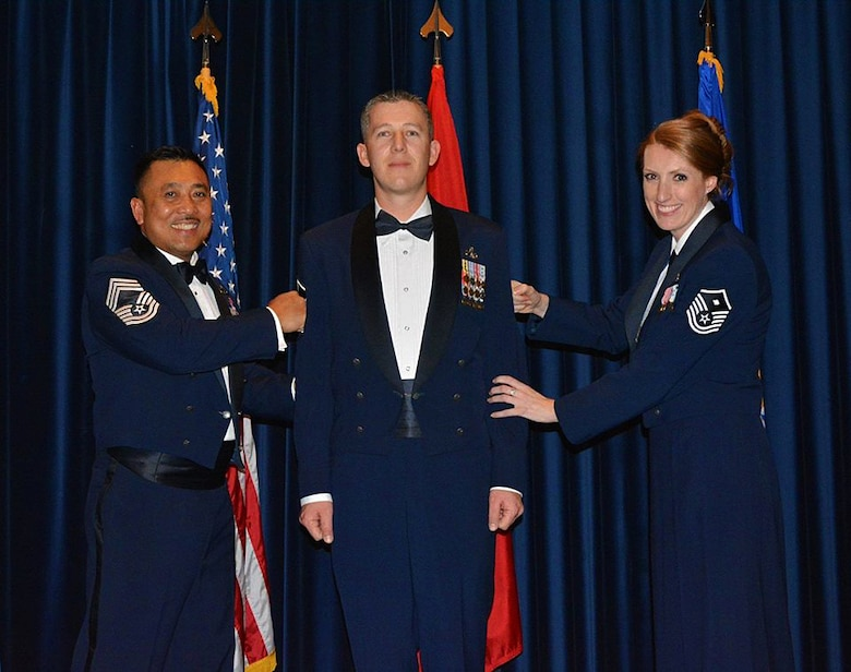 """Master Sgt. Chris Rekrut, 728th Air Mobility Squadron Quality Assurance superintendent, is """"tacked on"""" by Chief Master Sgt. Phillip Gawan, 728th superintendent, and his wife, Air Force Reserve Master Sgt. Corrine Rekrut. Rekrut, was recently promoted by means of the Stripes for Exceptional Performers program for his sustained exceptional performance at work and his involvement in the community. (Photo by Carla Bigger)"""