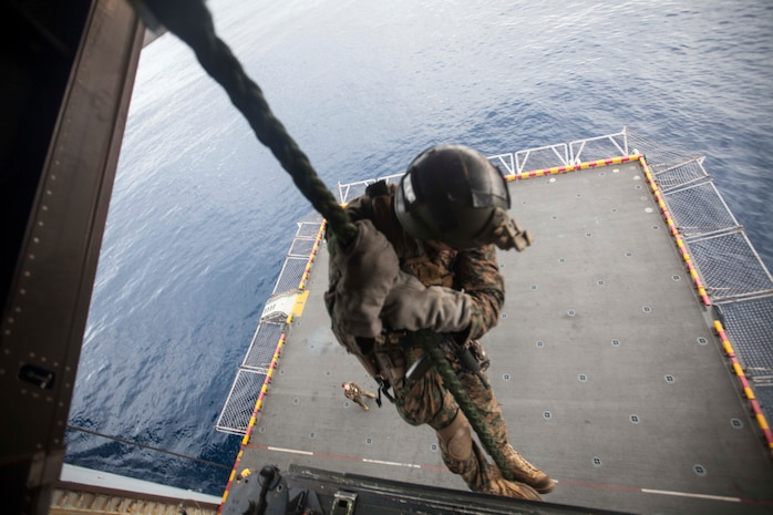 A Marine with the Maritime Raid Force, 31st Marine Expeditionary Unit, rappels from the back of an MV-22 Osprey onto the port-side elevator of the USS Bonhomme Richard (LHD 6) during a static fast-rope training event here, Mar. 1. The event was in preparation for certification exercises and also gave other Marines and sailors an opportunity to learn the skill. The 31st MEU is currently conducting amphibious integration training alongside Amphibious Squadron 11 while deployed for its regularly scheduled Spring Patrol.