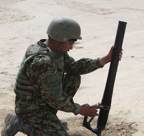 A soldier with 7th Kandak, 215th Corps, Afghan National Army, slowly squeezes the trigger of a M224 60 mm Lightweight Company Mortar System during a live-fire training exercise that marked the conclusion of a four-week mortarman's course aboard Camp Shorabak, Afghanistan Mar. 5, 2014. The course instilled basic mortar man skills as well as taught explosive ordnance disposal skills to approximately 40 ANA soldiers. The ANA soldiers newly acquired training will give them an advantage on the battlefield as they return to their units throughout Afghanistan. (U.S. Marine Corps photo by Cpl. Cody Haas/ Released)