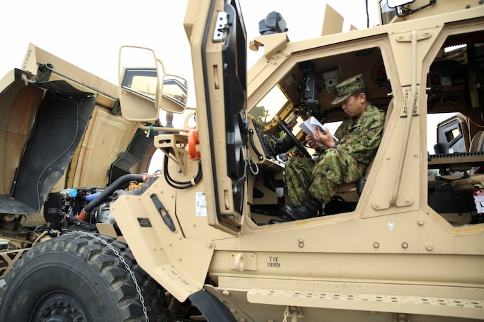 A member of the Japanese Ground Self-Defense Force reads while sitting in a Mine-Resistant Ambush Protected All-Terrain vehicle, Feb. 27, 2014, during an English clinic aboard Marine Corps Air Station Iwakuni, Japan. Marine Wing Support Squadron 171 set up a static display of their vehicles for the visit.