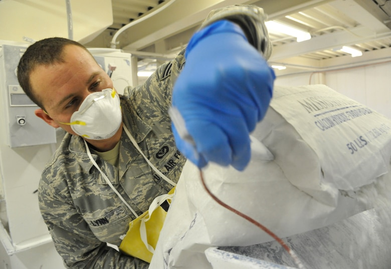 U.S. Air Force Senior Airman Brandon Lynn, 509th Civil Engineer Squadron water and fuels maintenance journeyman, opens a bag of lime at Whiteman Air Force Base, Mo., Feb. 27, 2014. This procedure ensures lime is constantly fed to the softening basin to maintain pH and remove high calcium carbonate hardness from the water. (U.S. Air Force photo by Airman 1st Class Keenan Berry/ Released)