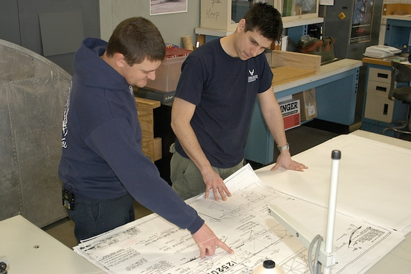 DAYTON, Ohio -- National Museum of the U.S. Air Force restoration specialists Nick Almeter and Casey Simmons examine blue prints for the Stearman PT-13D Kaydet.  Plans call for the aircraft to be part of an expanded Tuskegee Airman exhibit in the World War II Gallery at the National Museum of the U.S. Air Force. (U.S. Air Force photo by Ken LaRock)