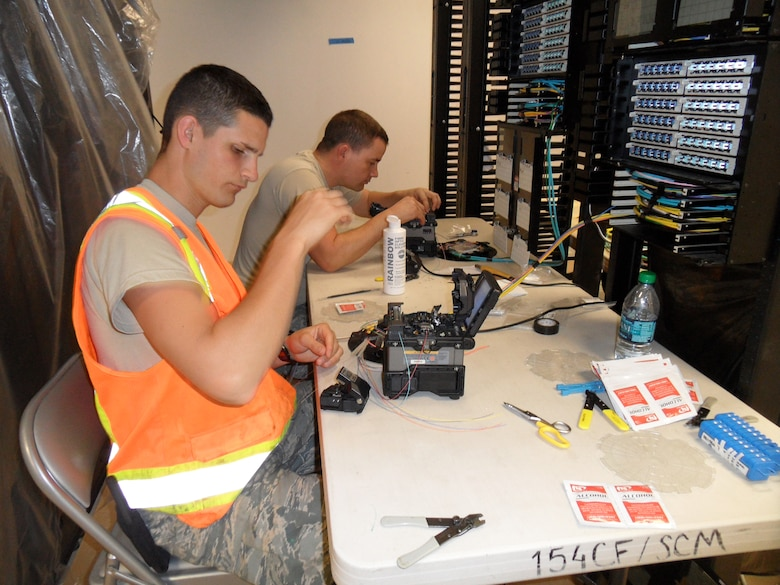 Airman 1st Class Alex Bernier and Staff Sgt. Lamont Class splice fiber optic cable in preparation to transfer communication equipment from a temporary shelter to a permanent facility at Joint Base Pearl Harbor-Hickam.  (Utah Air National Guard photo by MSgt. Mark Hoferitza/RELEASED)