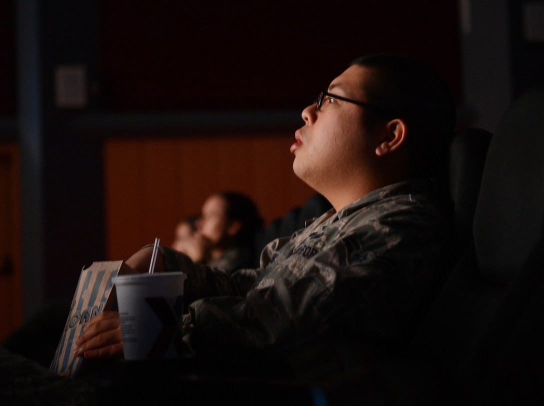 """U.S. Air Force Airman 1st Class Jan-Michael Cruz, 52nd Fighter Wing command section executive administrator, watches the documentary film """"Ghost Army"""" in the Skyline Theater at Spangdahlem Air Base, Germany, March 11, 2014. The World War II documentary chronicles the history of a secret U.S. Army unit whose mission was to mislead and deceive the enemy with various tactics including recorded battle sounds, inflatable tanks and false radio traffic. (U.S. Air Force photo by Staff Sgt. Chad Warren/released)"""