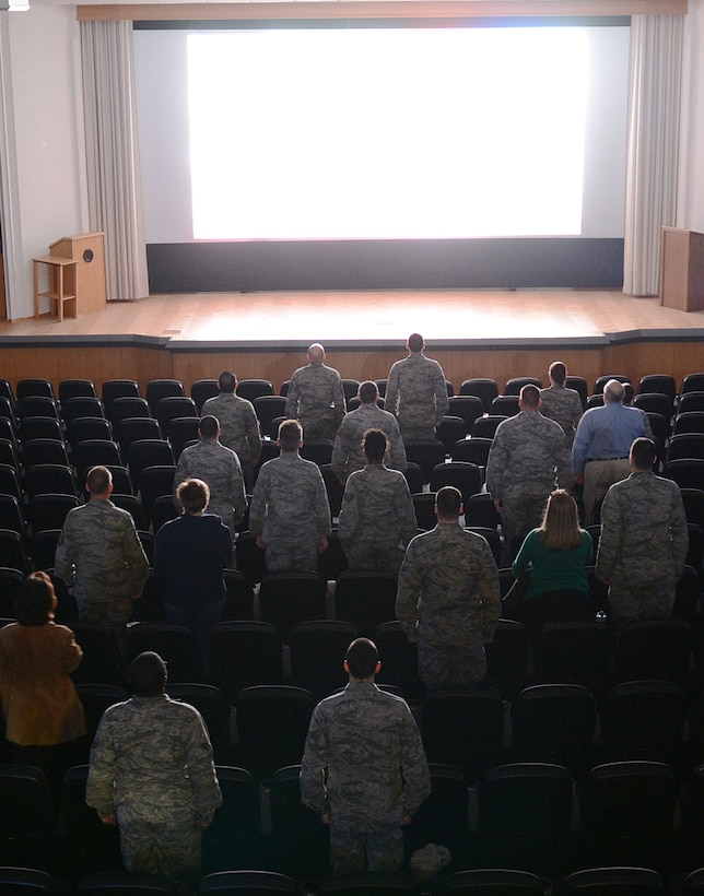 """Patrons stand for the national anthem before the showing of """"Ghost Army"""" in the Skyline Theater at Spangdahlem Air Base, Germany, March 11, 2014. The documentary chronicles the history of a secret World War II U.S. Army unit whose mission was to mislead and deceive the enemy with various tactics including recorded battle sounds, inflatable tanks and false radio broadcasts. (U.S. Air Force photo by Staff Sgt. Chad Warren/released)"""