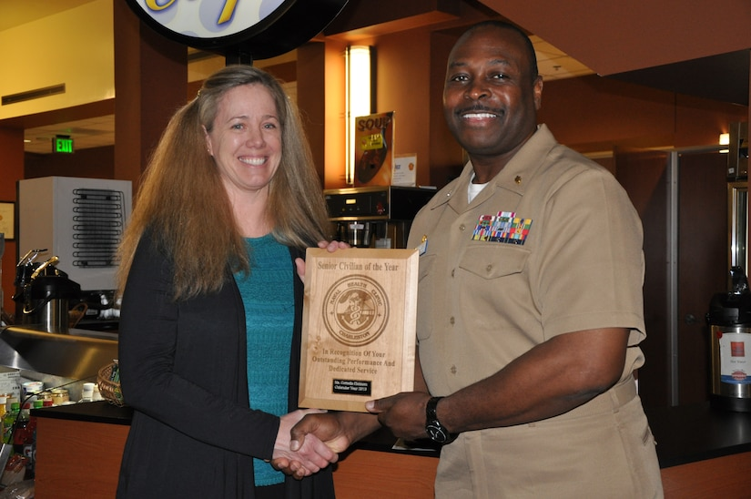 Capt. Marvin Jones, Naval Health Clinic Charleston commanding officer, presents Lynn Eichhorn, NHCC infection prevention and control nurse, a plaque honoring her as NHCC Senior Civilian of the Year for 2013, during a ceremony March 7, 2014, at NHCC on Joint Base Charleston – Weapons Station, S.C. (U.S. Navy photo)