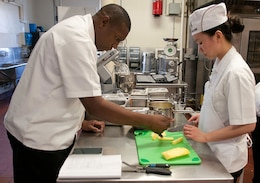 Sgt. Jeffrey Matthews (left), DHHB, 1st Inf. Div., team captain and coach of the 1st Inf. Div. Culinary Arts Team, gives pointers to Spc. Yin Jenkins, 2nd GSAB, 1st Avn. Regt., CAB, 1st Inf. Div., Feb. 20 at Fort Riley's Food Service Lab. This will be Matthews third time at the Annual Military Culinary Arts Competitive Training Event at Fort Lee, Va., but for Jenkins and several other members of the team, it will be a first.