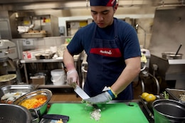Mario Moreno, a Sodexo employee from Marine Corps Recruit Depot San Diego, chops onions during the Marine Corps Installations-West Chef of the Quarter Culinary Competition hosted by the 41-Area Mess Hall here, March 12. Kenny Ponce and Sid Hilarides, Sodexo employees from 53-Area Mess Hall, were awarded first place for second quarter of fiscal year 2014. Ponce and Hilarides took first in the third quarter, 2013 competition as well.