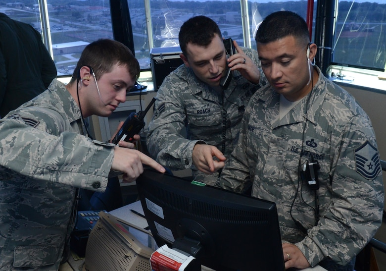(From left) U. S. Air Force Senior Airmen Michael-Paul Kendall, Shaun Roach, and Master Sgt. Joseph Arce, 36th Operations Support Squadron air traffic controllers, look at the daily events log Feb. 24, 2014, on Andersen Air Force Base, Guam, during Exercise Cope North 2014. The exercise, which is a joint effort between the U.S. Air Force, the Japan Air Self-Defense Force and the Royal Australian Air Force, is designed for allies to work together on both humanitarian assistance and disaster relief (HA/DR) missions as well as large force employment mission with dissimilar aircraft. (U.S. Air Force photo by Airman 1st Class Emily A. Bradley/Released)